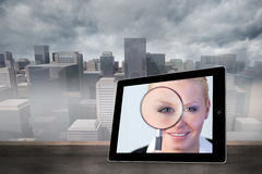 Composite image of businesswoman holding magnfying glass on tablet screen Royalty Free Stock Photo