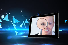 Composite image of businesswoman holding magnfying glass on tablet screen stock photo