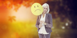 Composite image of  businesswoman holding sad smiley face Stock Photo