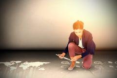 Composite image of businesswoman kneeling while using digital tablet. Businesswoman kneeling while using digital tablet against grey room Stock Photography