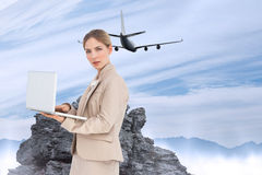 Composite image of businesswoman with a laptop Stock Photo