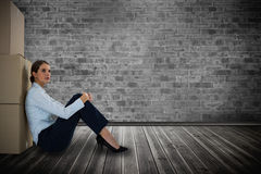 Composite image of businesswoman leaning on cardboard boxes against white background royalty free stock image