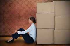 Composite image of businesswoman leaning on cardboard boxes against white background Stock Image