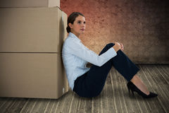 Composite image of businesswoman leaning on cardboard boxes against white background stock images