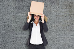 Composite image of businesswoman lifting box off head Royalty Free Stock Photography