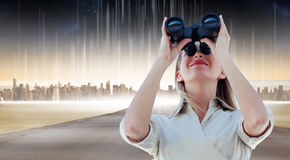 Composite image of businesswoman looking through binoculars Stock Photo