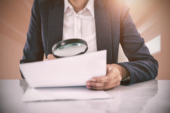 Composite image of businesswoman looking at document through magnifying glass Stock Photo