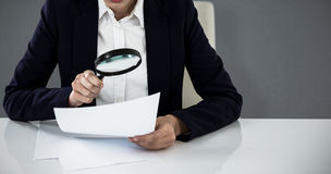 Composite image of businesswoman looking at document through magnifying glass Royalty Free Stock Photo