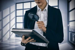 Composite image of businesswoman looking at document through magnifying glass. Businesswoman looking at document through magnifying glass against room with large Royalty Free Stock Photo