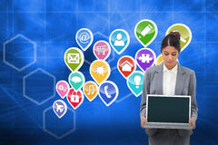 Composite image of businesswoman looking at laptop in her hands Royalty Free Stock Image