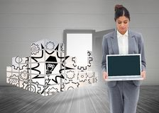 Composite image of businesswoman looking at laptop in her hands Stock Photo