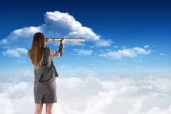 Composite image of businesswoman looking through a telescope Stock Images