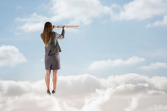 Composite image of businesswoman looking through a telescope Royalty Free Stock Photo