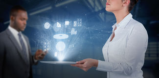 Composite image of businesswoman looking up while holding digital tablet Royalty Free Stock Photos
