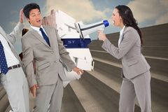 Composite image of businesswoman with megaphone yelling at colleagues Royalty Free Stock Images