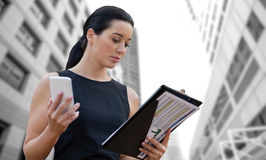 Composite image of businesswoman with mobile phone reading document Stock Photos