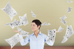 Composite image of businesswoman with an open hand to show flying sheets Royalty Free Stock Photos