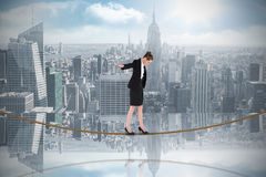 Composite image of businesswoman performing a balancing act on tightrope Royalty Free Stock Photos