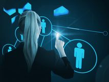 Composite image of businesswoman pointing on glowing futuristic blue background Royalty Free Stock Photography