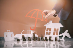 Composite image of businesswoman protecting her wealth with umbrella Royalty Free Stock Images