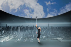 Composite image of businesswoman pulling down blue sky Royalty Free Stock Images