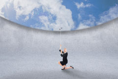Composite image of businesswoman pulling down blue sky Stock Photography