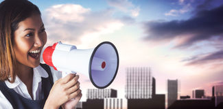Composite image of businesswoman shooting through a megaphone Royalty Free Stock Photo