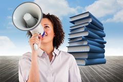 Composite image of businesswoman shouting through megaphone Stock Image