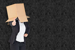 Composite image of businesswoman showing thumbs up with box over head Stock Photography