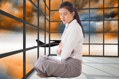 Composite image of businesswoman sitting cross legged with arms crossed Royalty Free Stock Images