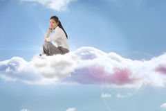 Composite image of businesswoman sitting cross legged with hands together Royalty Free Stock Images
