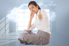 Composite image of businesswoman sitting cross legged showing thumb up Royalty Free Stock Photo