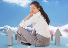 Composite image of businesswoman sitting cross legged smiling Royalty Free Stock Image