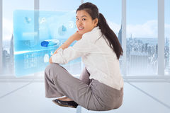 Composite image of businesswoman sitting cross legged smiling Royalty Free Stock Images