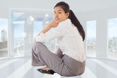 Composite image of businesswoman sitting cross legged smiling Stock Image