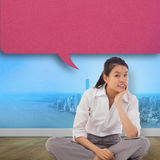 Composite image of businesswoman sitting cross legged thinking with speech bubble royalty free stock images