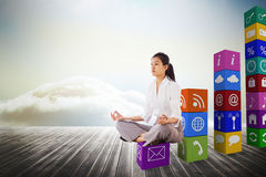 Composite image of businesswoman sitting in lotus pose Stock Photo