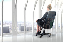 Composite image of businesswoman sitting on swivel chair in black suit Royalty Free Stock Photo