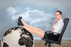Composite image of businesswoman sitting on swivel chair with feet up Royalty Free Stock Photo