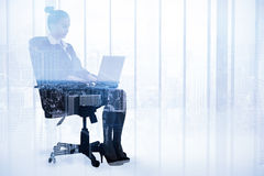 Composite image of businesswoman sitting on swivel chair with laptop Stock Photo