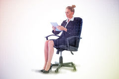 Composite image of businesswoman sitting on swivel chair with tablet Stock Images