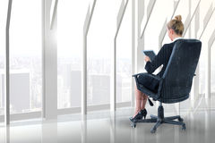 Composite image of businesswoman sitting on swivel chair with tablet Stock Photo