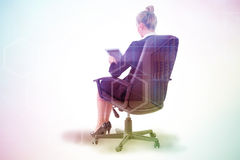 Composite image of businesswoman sitting on swivel chair with tablet Stock Photography