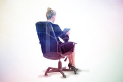 Composite image of businesswoman sitting on swivel chair with tablet Royalty Free Stock Photography