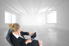 Composite image of businesswoman sitting on swivel chair with tablet Royalty Free Stock Images
