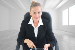 Composite image of businesswoman sitting on swivel chair with tablet Royalty Free Stock Photo