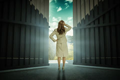 Composite image of businesswoman standing back to camera with hand on head 3d Royalty Free Stock Photo
