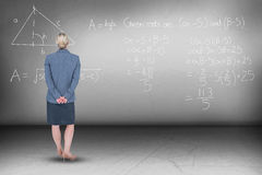 Composite image of businesswoman standing with hands behind back Stock Photo