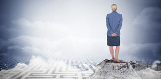Composite image of businesswoman standing with hands behind back Stock Photography