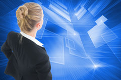 Composite image of businesswoman standing with hands on hips Stock Images